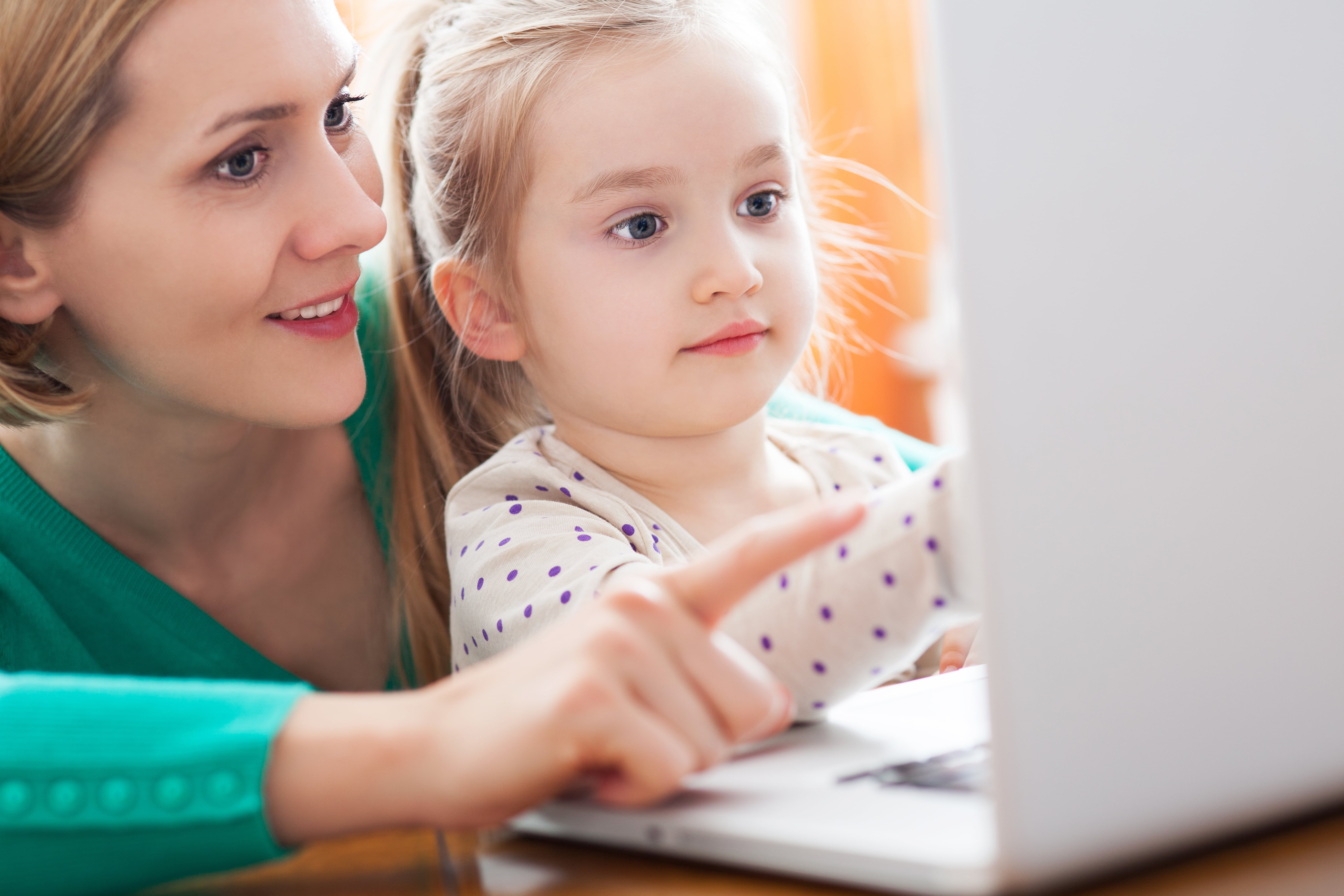 Child and mom looking at a Pc.